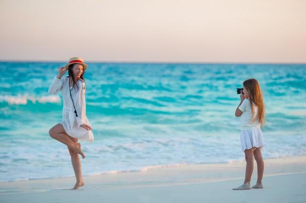 Niña linda que toma la foto de su madre en la playa tropical