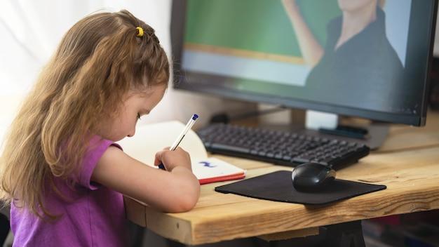 Una niña linda que usa una computadora para aprendizaje electrónico remoto, escribe en un cuaderno