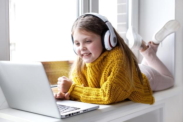 Niña linda que usa la computadora portátil para comunicarse en internet en casa