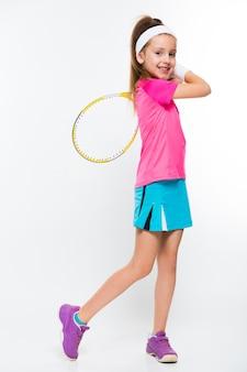 Niña linda con raqueta de tenis en sus manos