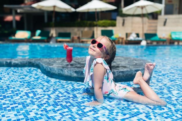 Niña linda relajante en la piscina