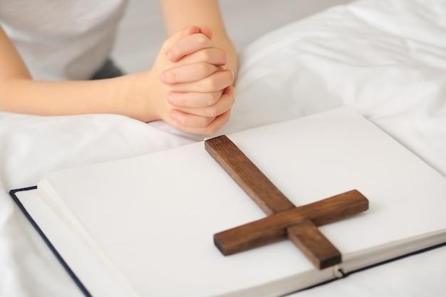 Niña linda rezando en casa, primer plano