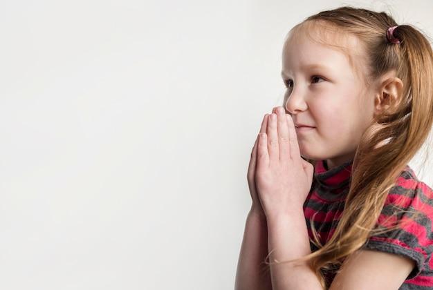 Niña linda rezando con espacio de copia