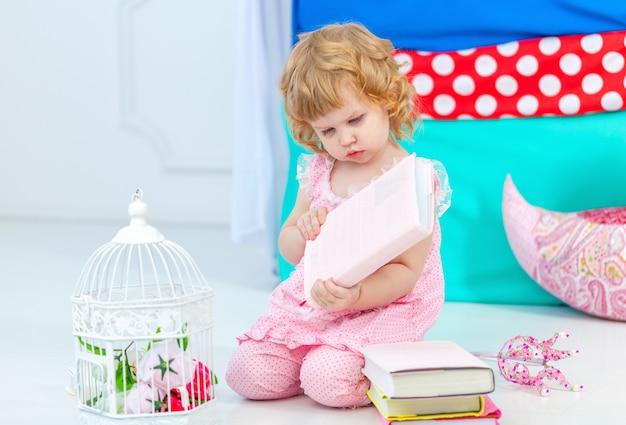 Niña linda rizada en pijama rosa mirando el libro sentado en el suelo en el dormitorio de los niños.