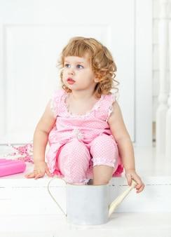 Niña linda y rizada con un vestido rosa con lunares sentada en el porche blanco estilo provenzal
