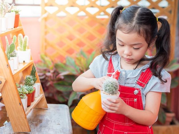 Niña linda rociando agua al cactus en el jardín del balcón de la casa.