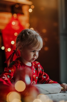 Niña linda rodando la masa para galletas de navidad