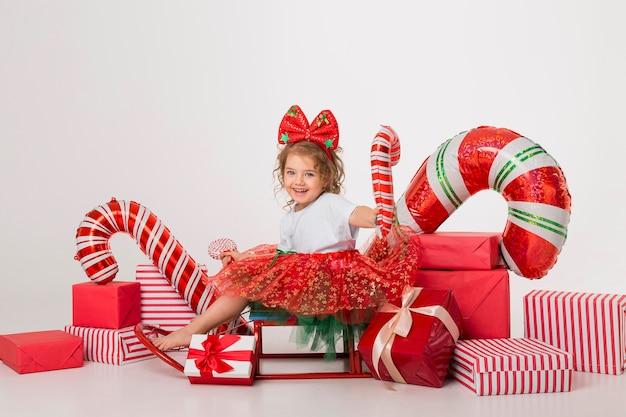 Niña linda rodeada de elementos navideños