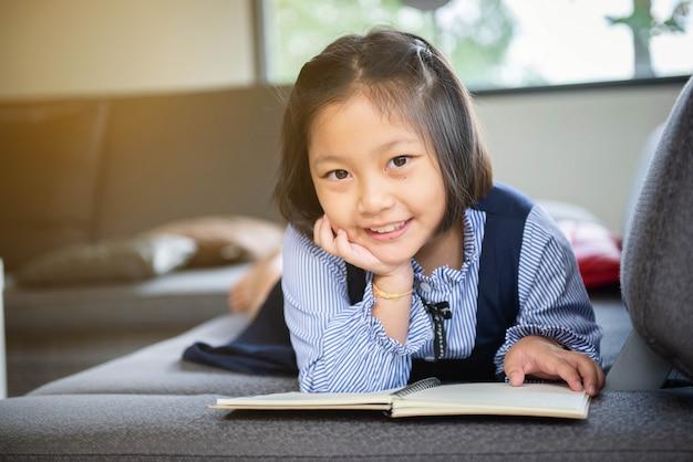 Niña linda en ropa casual que lee un libro y que sonríe mientras que miente en un sofá en el cuarto.