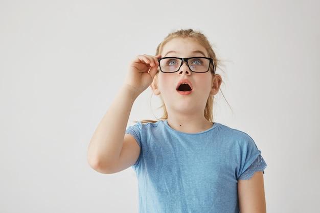 Niña linda rubia con preciosos ojos azules en camiseta azul y con gafas mira hacia arriba abriendo boca con sorpresa al ver una gran araña en la pared.