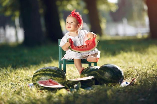 Niña linda con sandías en un parque