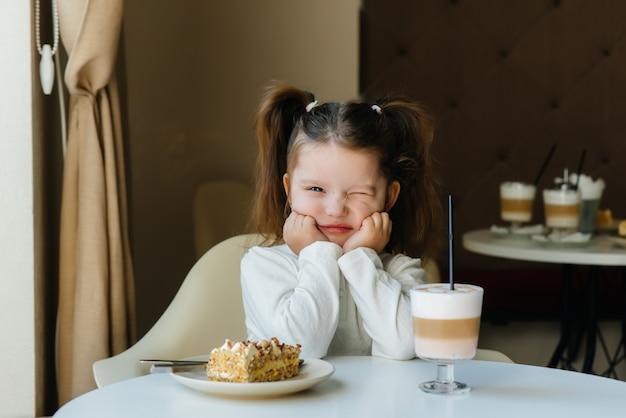 Una niña linda está sentada en un café y mirando un pastel y primer plano de cacao. dieta y nutrición adecuada.