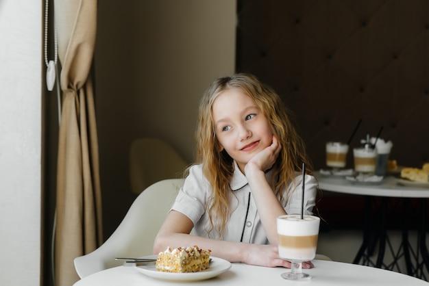 Niña linda está sentada en la cafetería y mirando pastel y coco