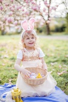 Niña linda sentada en el césped cerca de la magnolia. una niña vestida como un conejito de pascua sostiene una flor y un huevo. primavera.