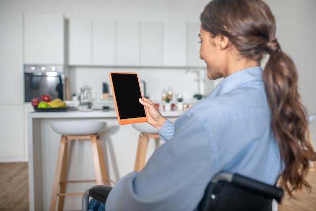 Una niña linda sentada en la cocina con un teléfono inteligente en las manos