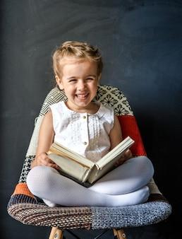 Niña linda sentada en una silla hermosa con un libro en la mano, el concepto de educación y vida escolar