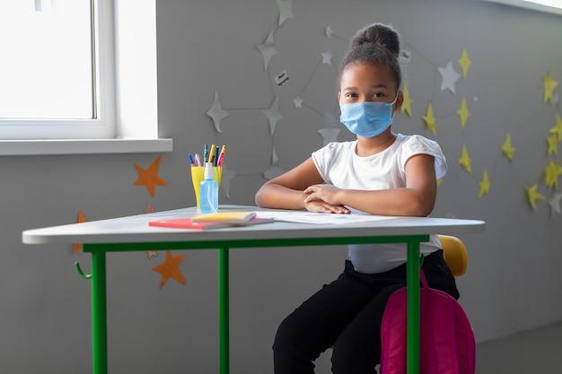 Niña linda sentada en su escritorio en el aula