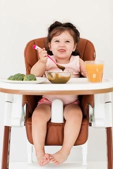 Niña linda sentada en su mesa delante de brócoli y jugo