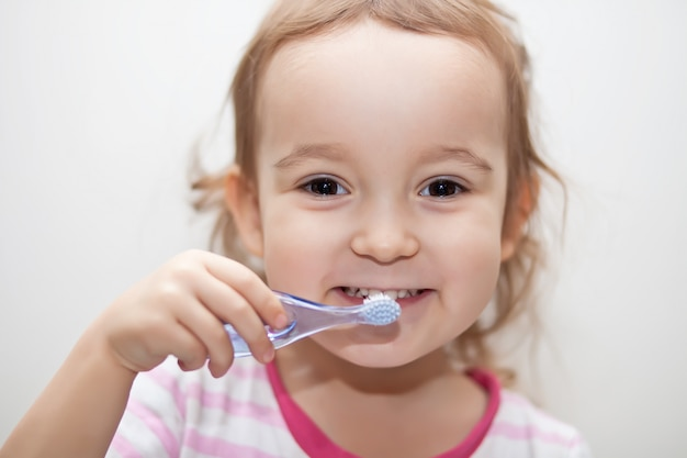 Niña linda smailing y cepillarse los dientes.