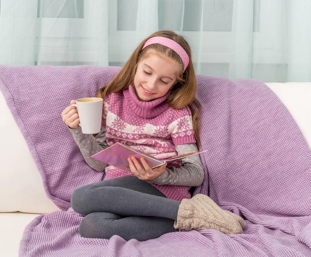 Niña linda en el sofá con la taza mirando una revista