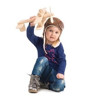 Niña linda en sombrero piloto con avión de madera