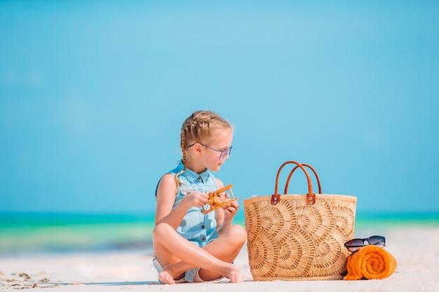 Niña linda con sombrero en la playa durante las vacaciones de verano