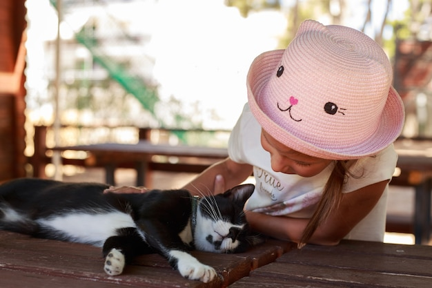 Niña linda con sombrero rosa acariciando un gato negro al aire libre