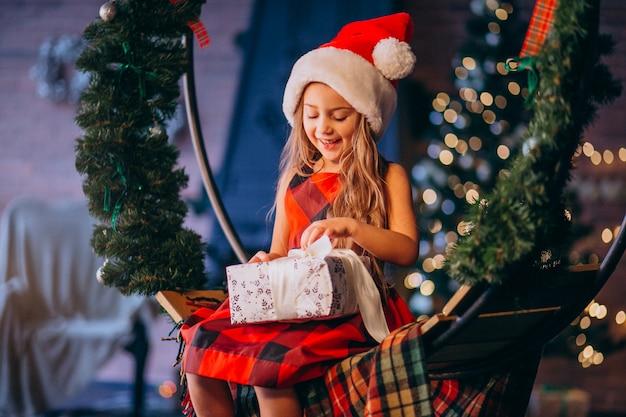 Niña linda en el sombrero de santa que desempaqueta el regalo de navidad