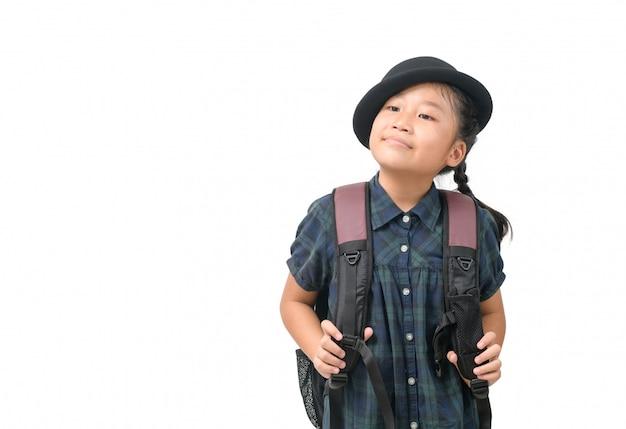 Niña linda con sombrero sonriendo y sosteniendo la mochila