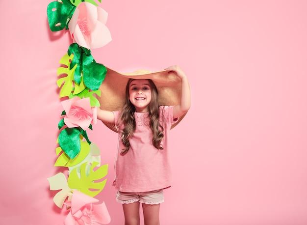 Niña linda con sombrero de verano sobre fondo de color