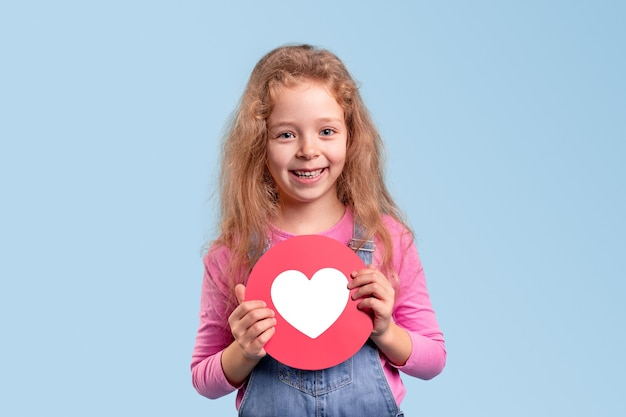 Niña linda sonriendo y demostrando el icono redondo rojo con el símbolo del corazón mientras representa la red social contra el fondo azul
