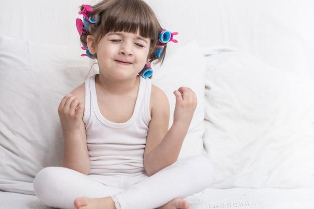 Niña linda sonriendo mientras está acostado en una acogedora cama blanca