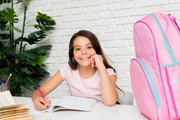 Niña linda sonriente haciendo la tarea en casa