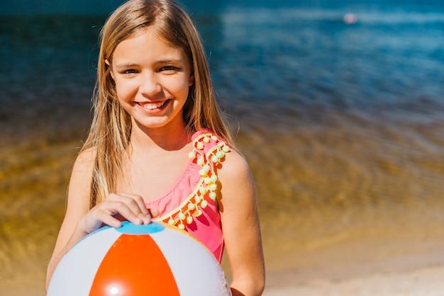 Niña linda sonriente con pelota de playa