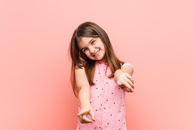 Niña linda sonrisas alegres apuntando al frente.