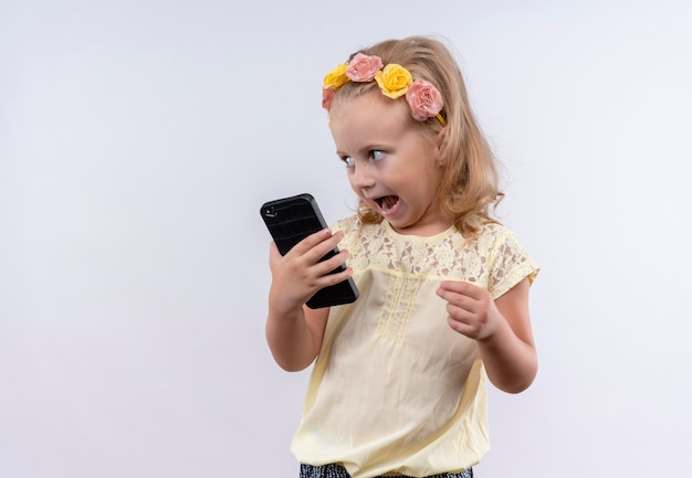 Una niña linda sorprendida con camisa amarilla en diadema floral sosteniendo el teléfono móvil en una pared blanca