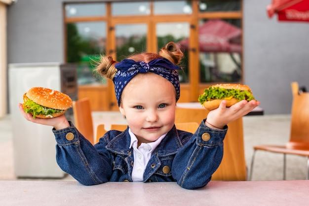 Niña linda sosteniendo dos hamburguesas en las manos en la cafetería de comida rápida