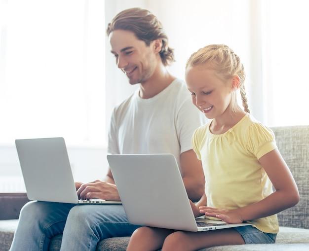 Niña linda y su apuesto padre están usando computadoras portátiles.