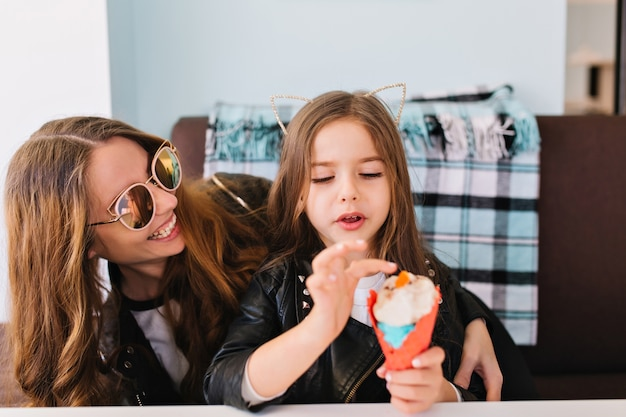 Niña linda y su atractiva mamá alegre con gafas de sol de moda divirtiéndose en casa y comiendo postre.