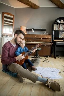 La niña linda y su hermoso padre están tocando la guitarra y sonriendo mientras están sentados en la habitación