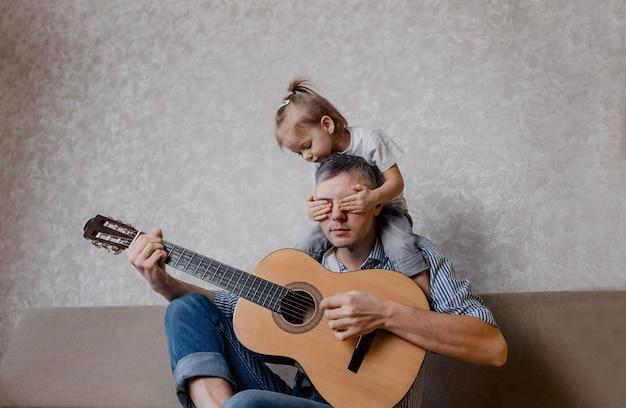 Niña linda y su padre guapo tocan la guitarra y sonríen sentados en el sofá de casa. dia del padre. cuidado y educación de los niños.