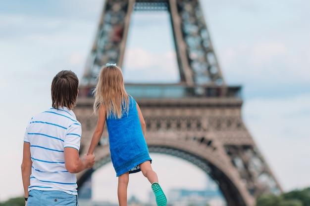 Niña linda y su padre en parís cerca de la torre eiffel durante las vacaciones de verano en francia