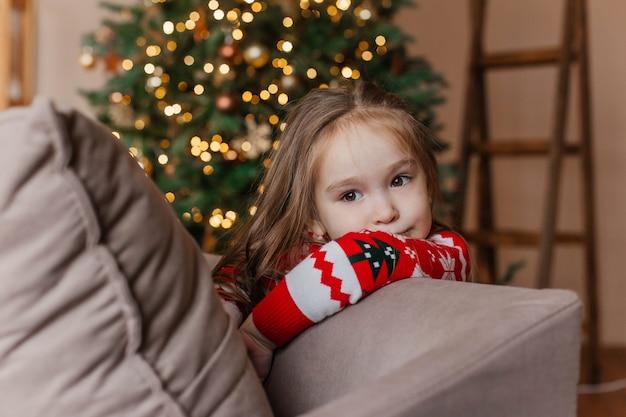 Niña linda en suéter rojo de navidad juega junto al árbol de navidad en casa. decoración de año nuevo.