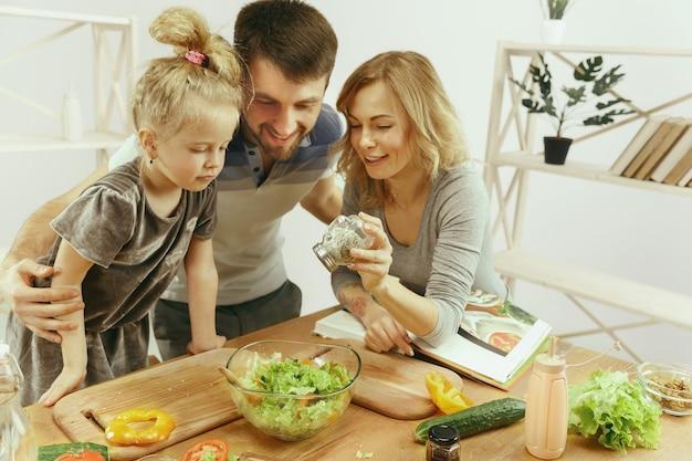 Niña linda y sus hermosos padres están cortando verduras en la cocina de casa