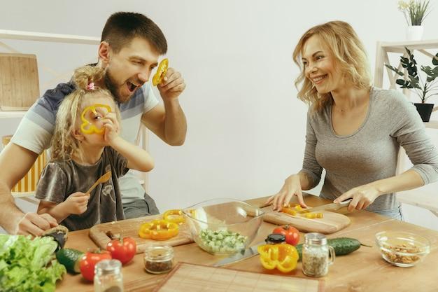 Niña linda y sus hermosos padres están cortando verduras y sonriendo mientras hacen ensalada