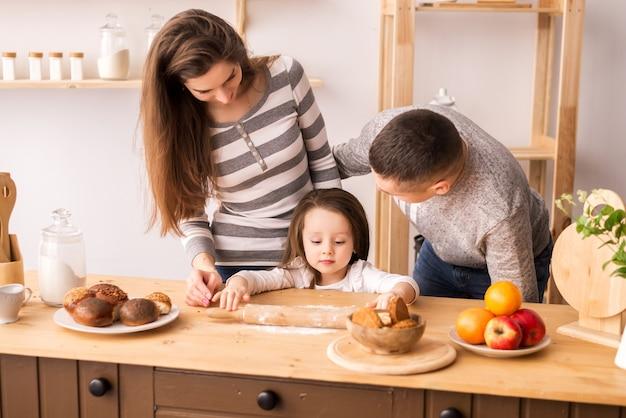 Niña linda y sus hermosos padres preparan la comida y sonríen mientras cocina en la cocina de su casa. amasar la masa en panqueques y panecillos