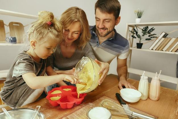Niña linda y sus hermosos padres preparando la masa para el pastel en la cocina de casa