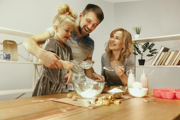 Niña linda y sus hermosos padres preparando la masa para el pastel en la cocina de casa.