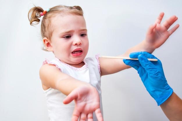 Niña linda temiendo al pediatra que examina