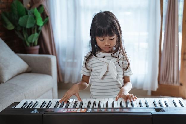 Niña linda toca un instrumento de teclado